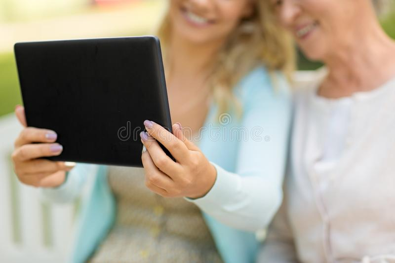 Adult daughter and senior mother with tablet pc royalty free stock image