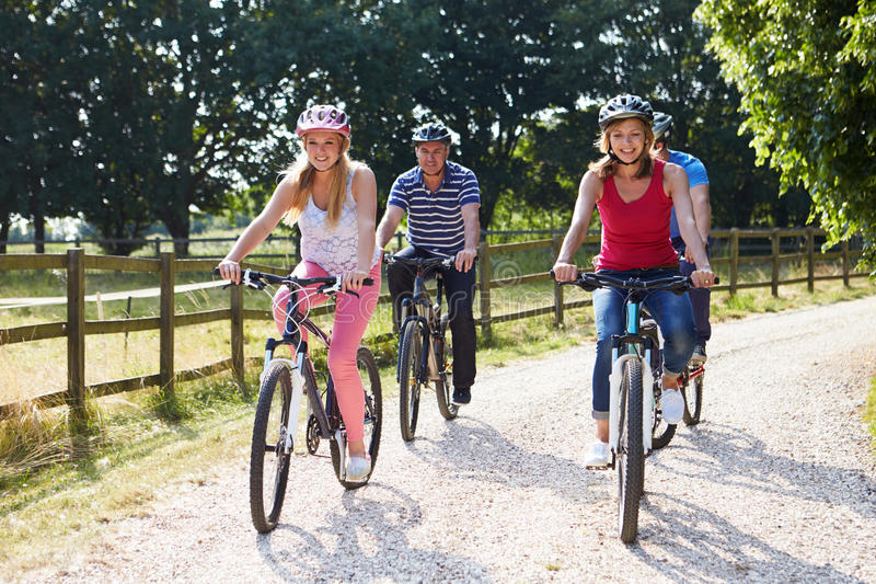 Family With Teenage Children On Cycle Ride In Countryside. Wearing Helmets stock photo