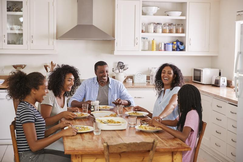 Family With Teenage Children Eating Meal In Kitchen stock images