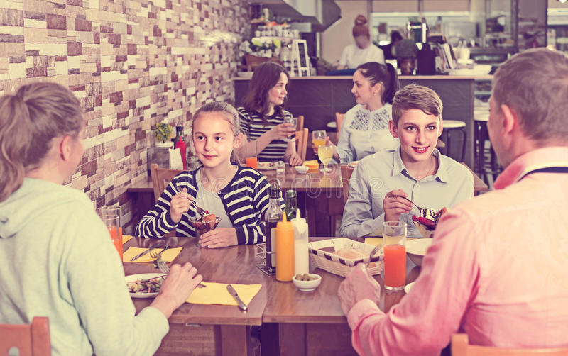 Family with teenage children enjoying meal in cafe. Positive russian family with teenage children enjoying meal in cafe stock photography