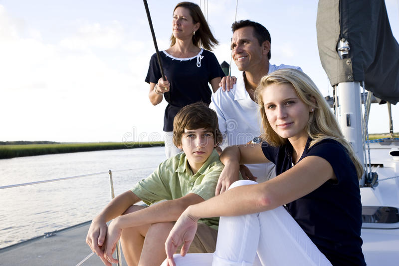 Family with teenage children sitting on boat. At dock on sunny day royalty free stock image