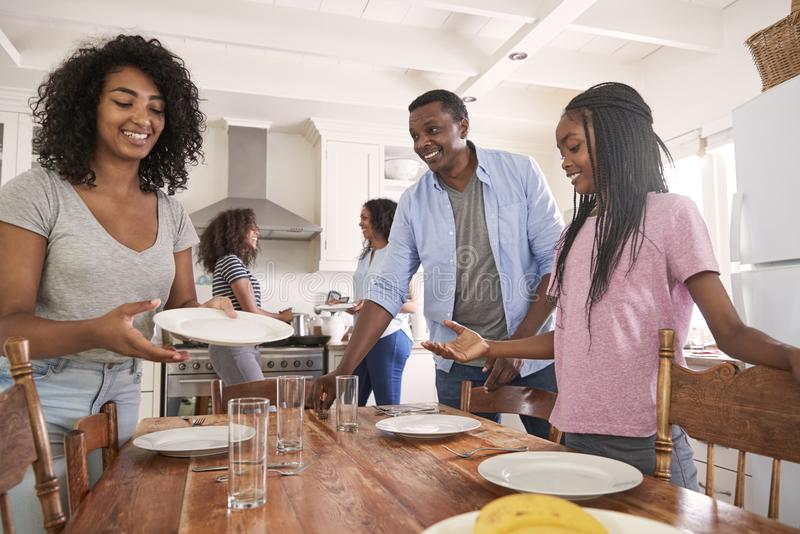 Family With Teenage Daughters Laying Table For Meal In Kitchen stock photography