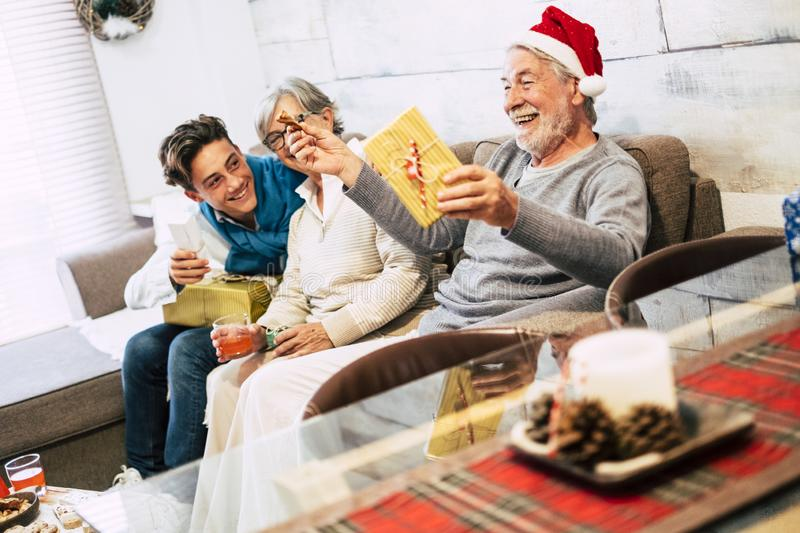 Family with teenager and grandfathers sitted at the sofa at home the morning of christmas laughing and openening their presents. With a lot of love and stock photos