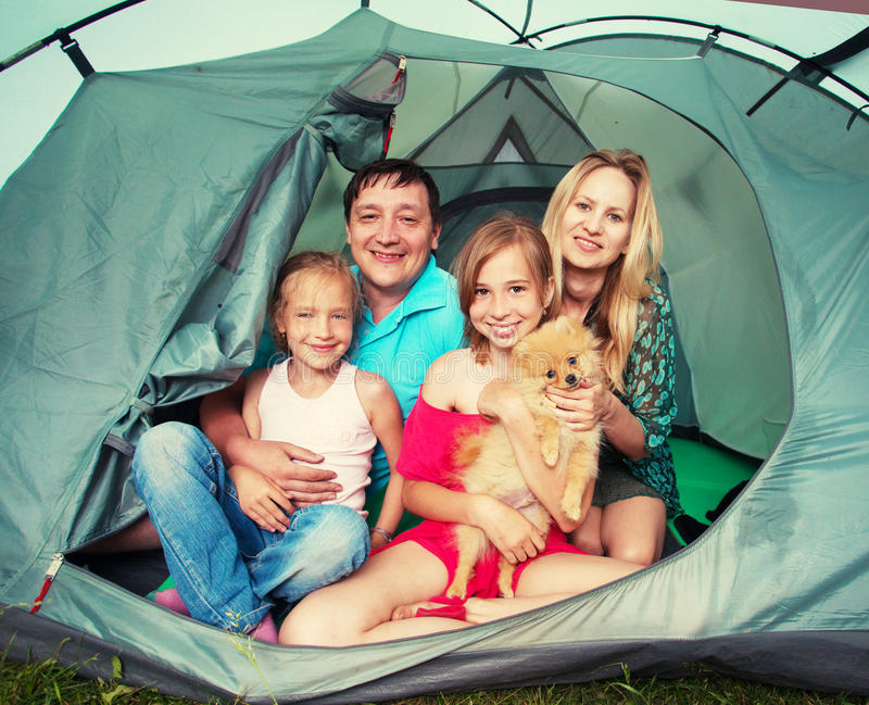 Family in a tent. Family with children in a tent. Camping. Happy parents with kids at summer vacations royalty free stock photo