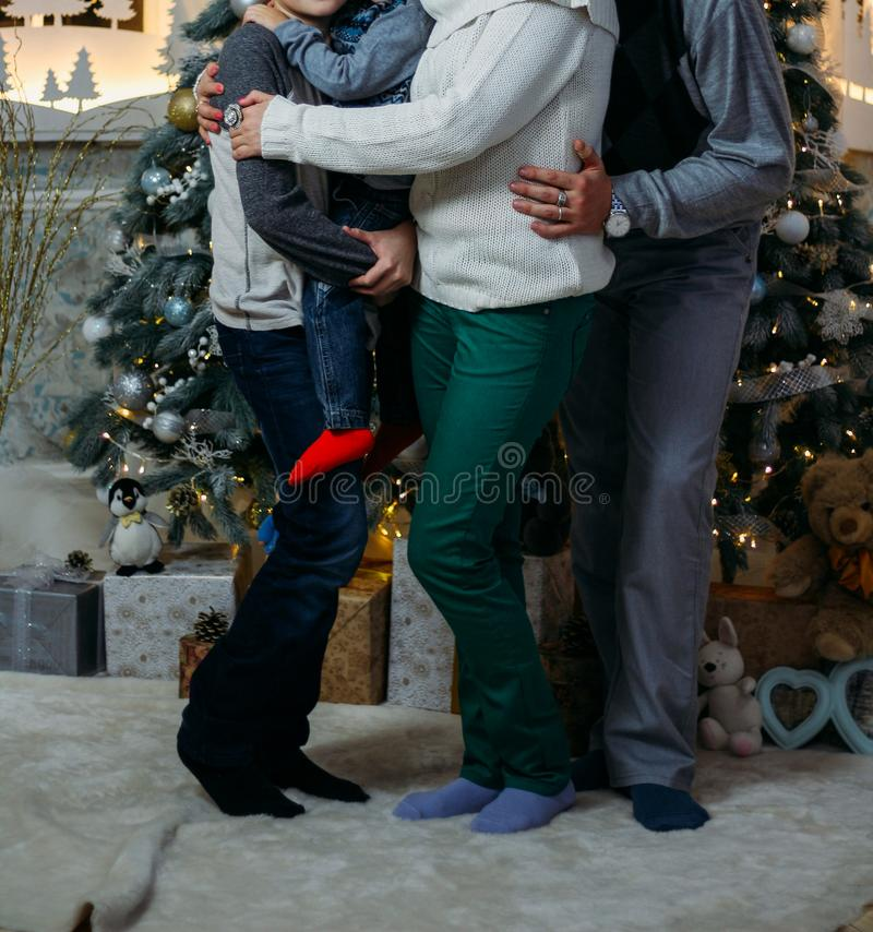 The family of their four people hugging against the background of the Christmas tree. parents and two children. Family photo, phot stock photo