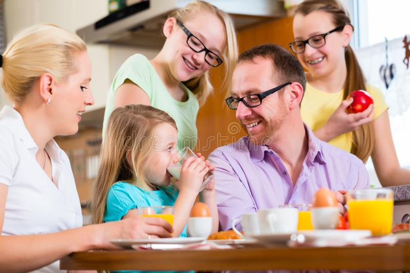 Family at home having breakfast in kitchen. Family in their home having breakfast with eggs, fruit, coffee and juice royalty free stock image