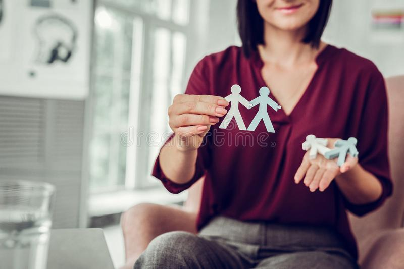 Family therapist holding little model of married couple in hand. Holding model. Family therapist wearing stylish clothes holding little model of married couple stock images