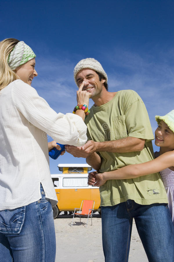Family of three on beach, woman applying sunscreen to man`s nose, daughter (5-7) embracing father, low angle view royalty free stock photography