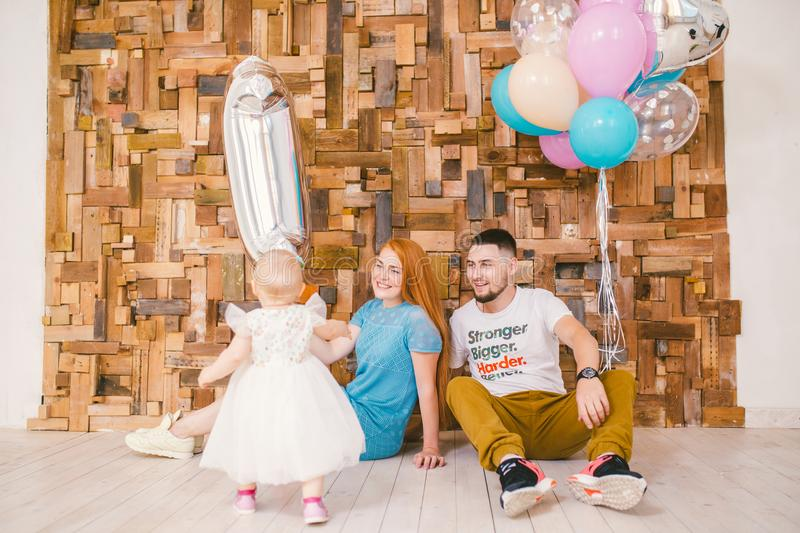 Family of three celebrates daughter`s birthday one year inside the room sitting on the floor against the background of the wooden stock photo