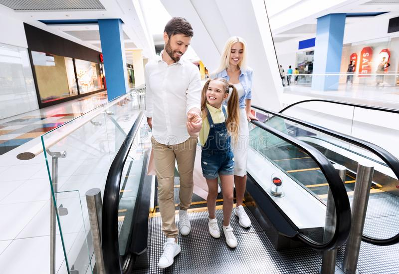 Family Doing Shopping Getting Off Escalator Holding Bags In Hypermarket. Family Of Three Doing Shopping Getting Off Escalator Moving Stairs Holding Shopper Bags royalty free stock photo