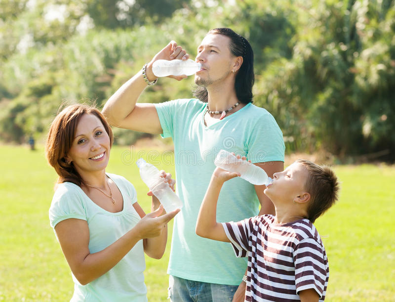 Family of three drinking from plastic bottles royalty free stock photos