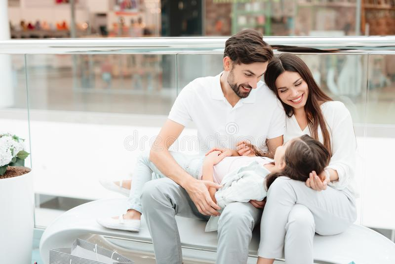 Family of three, father, mother and daughter are sitting on bench in shopping mall. stock photo