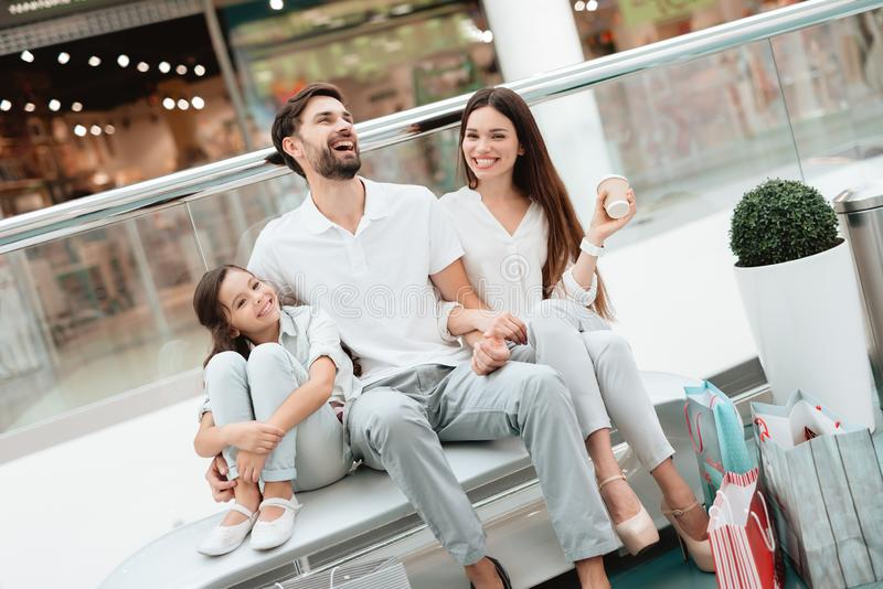 Family of three, father, mother and daughter are sitting on bench in shopping mall. stock photos