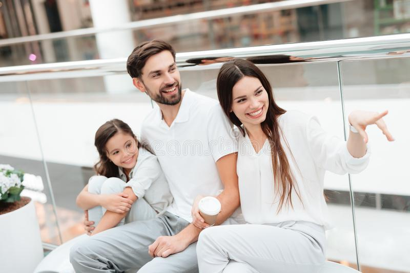 Family of three, father, mother and daughter are sitting on bench in shopping mall. royalty free stock image