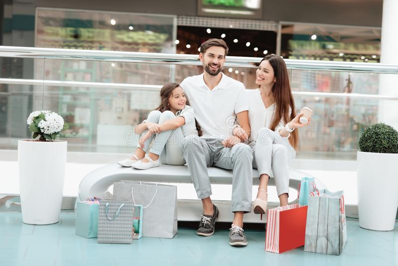 Family of three, father, mother and daughter are sitting on bench in shopping mall. royalty free stock images