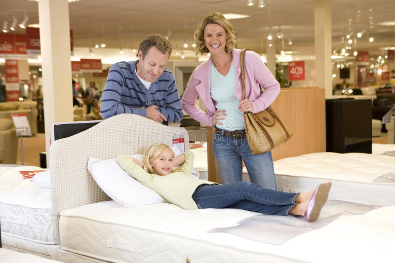 Family of three in furniture shop, daughter (6-8) on bed, smiling, portrait royalty free stock photos