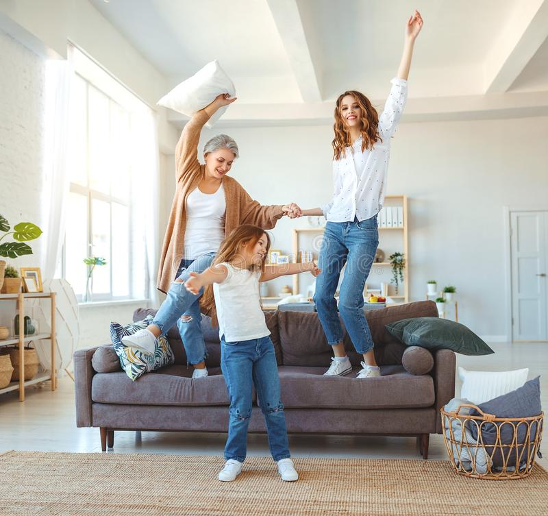Family three generations  grandmother, mother and child dancing, jumping and laugh at home. Happy family three generations   grandmother, mother and child royalty free stock photo