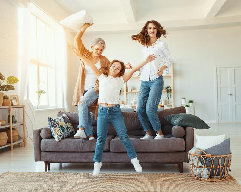 Family three generations  grandmother, mother and child dancing, jumping and laugh at home. Happy family three generations   grandmother, mother and child royalty free stock photography