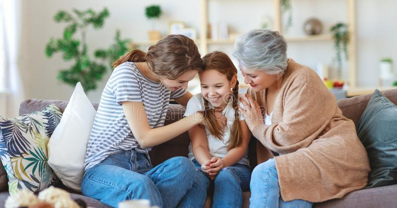 Family three generations  grandmother, mother and child play and laugh at home. Happy family three generations   grandmother, mother and child play and laugh at royalty free stock photography