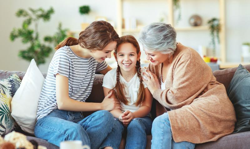 Family three generations  grandmother, mother and child play and laugh at home. Happy family three generations   grandmother, mother and child play and laugh at stock image