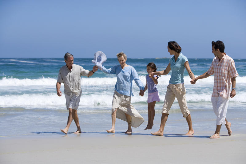 Family of three generations walking on beach, holding hands royalty free stock images