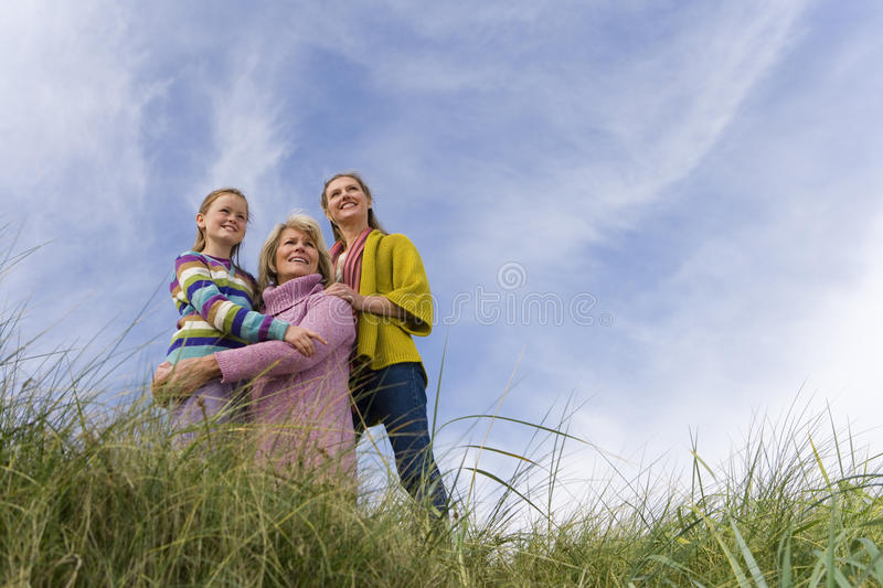 Family of three generations of women on sand dune, smiling, low angle view stock photo