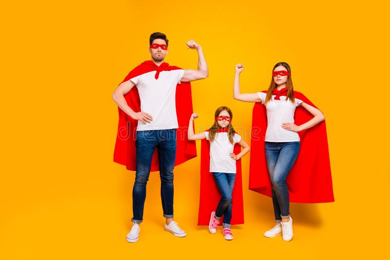 Family of three members playing cartoon incredible characters wear superhero costume isolated yellow background. Family of three members, playing cartoon royalty free stock photo