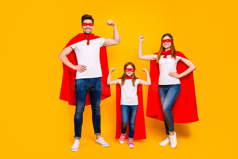 Family of three members playing cartoon incredible characters wear superhero costume isolated yellow background. Family of three members, playing cartoon royalty free stock images