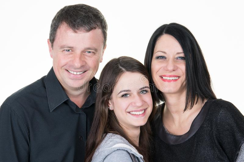 Family of three parents with their pretty teenager daughter. Happy family of three parents with their pretty teenager daughter royalty free stock photos