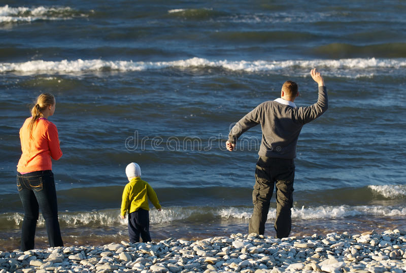 Family of three on pebble beach royalty free stock photography