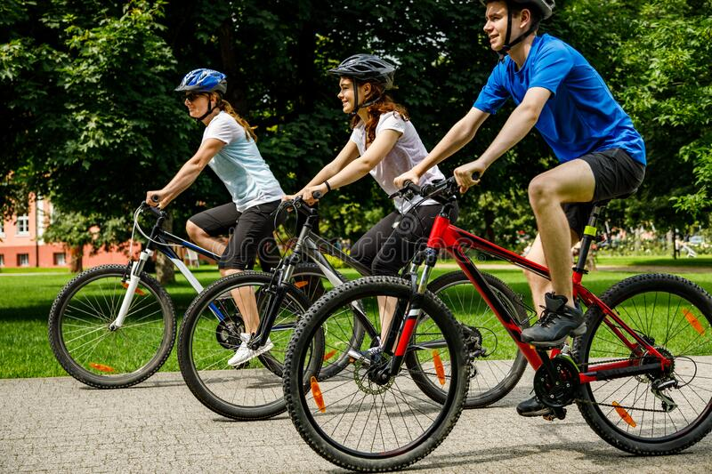 Family of three people riding bikes in summer park royalty free stock photo