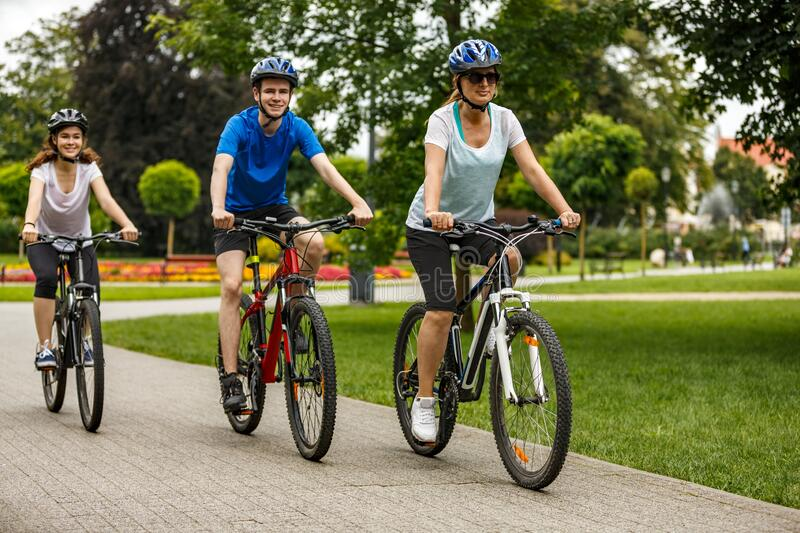 Family of three people riding bikes in summer park royalty free stock photography