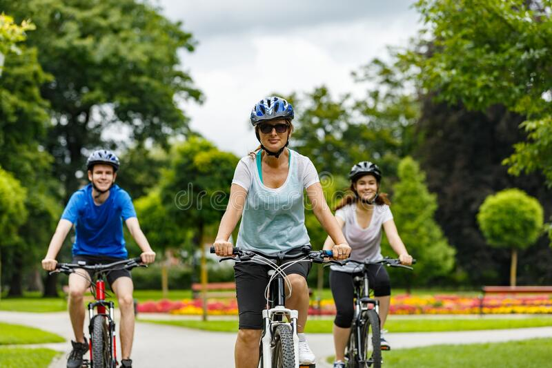 Family of three people riding bikes in park stock images
