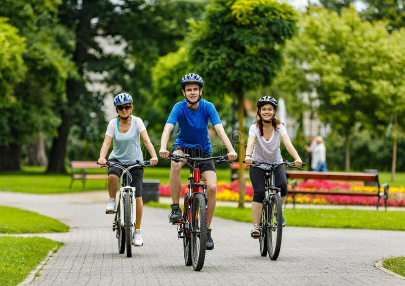 Family of three people riding bikes in summer park stock photos