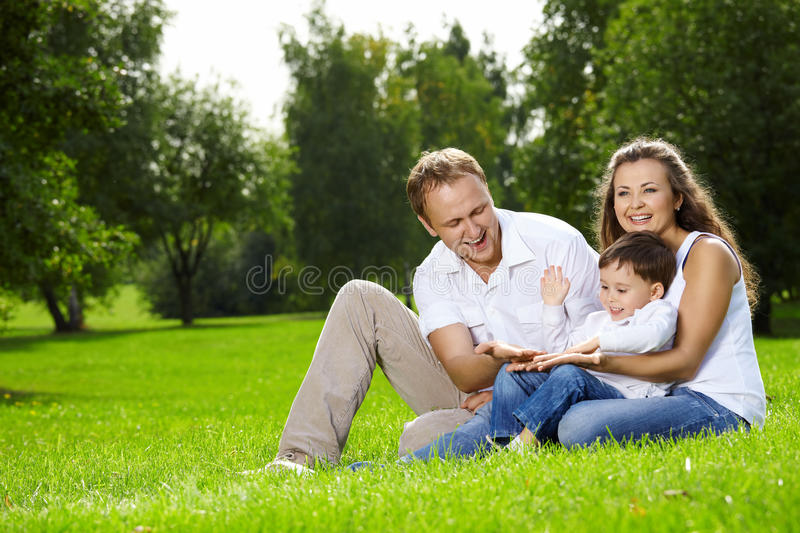 Family from three persons. Mother, father and small son have a rest on lawn in summer park stock photo