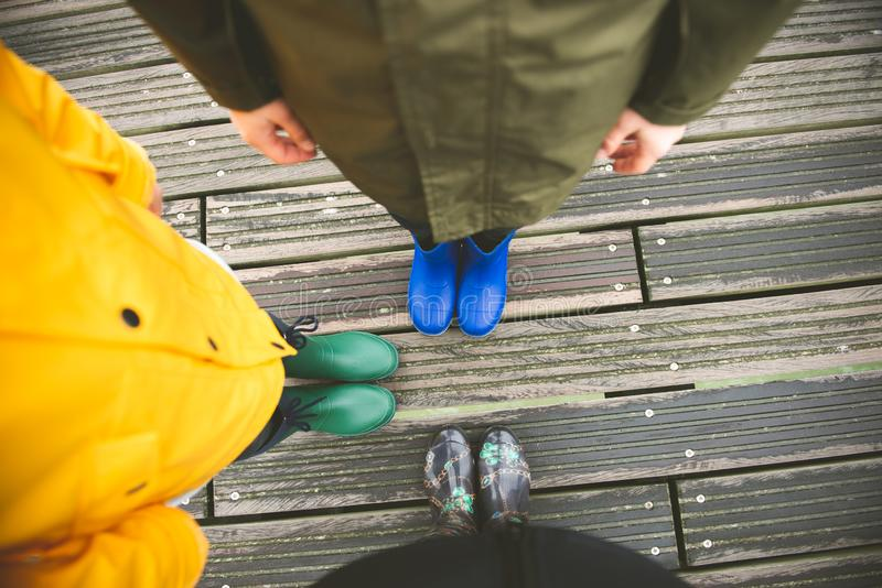 Family of three standing on woode pier in high rubber boots stock photography