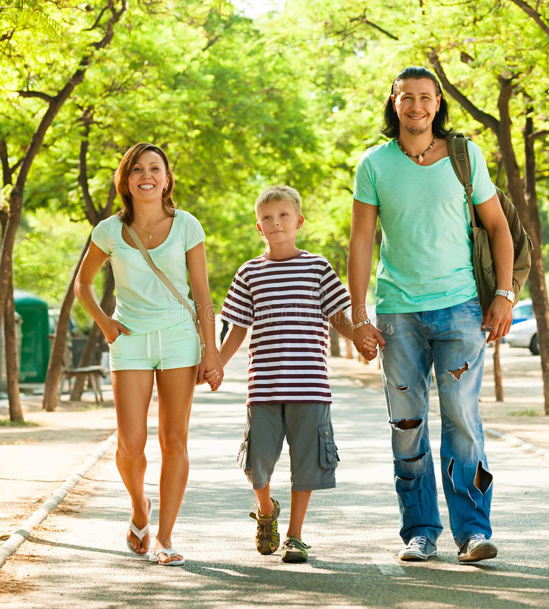 Family of three with teenager child. In summer street royalty free stock image