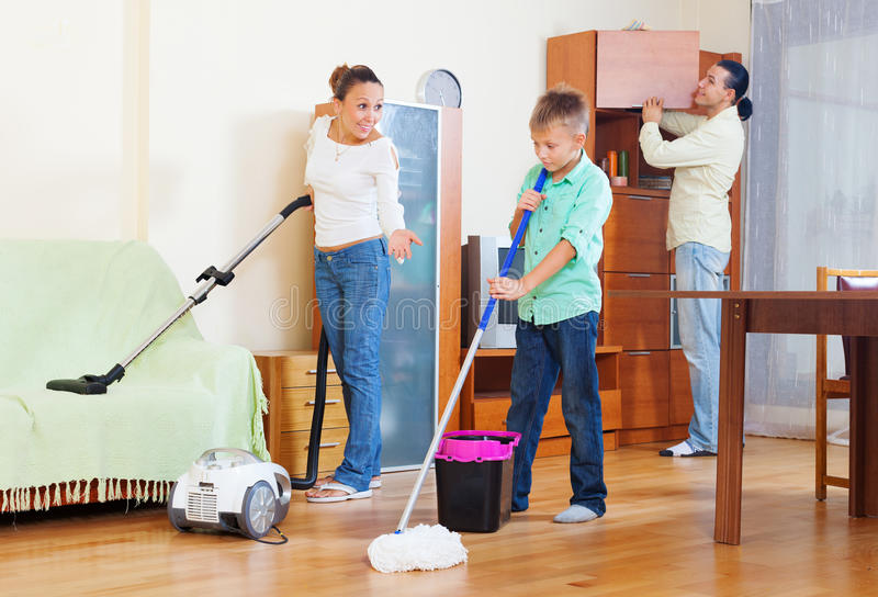 Family of three with teenager doing housework. With cleaning equipment royalty free stock photography