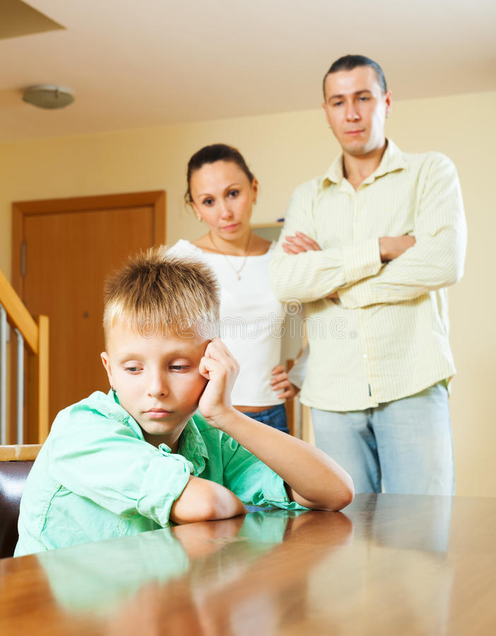Family of three with teenager having conflict. Ordinary family of three with teenager having conflict at home. Focus on boy stock photos