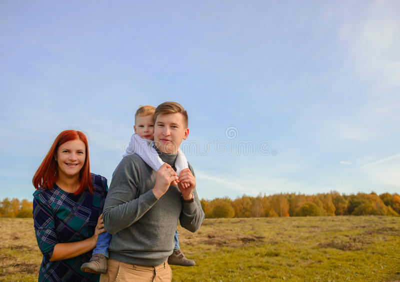 Family of three walking outdoors stock photography