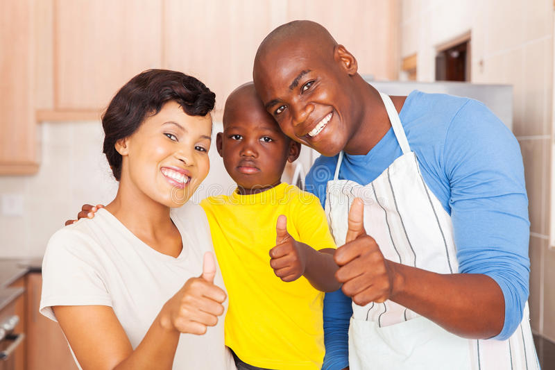 Family thumbs up. Happy young african family giving thumbs up in kitchen royalty free stock photos