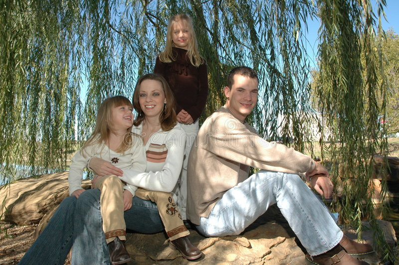 Family Time. An american family take their portraits in nature sitting outside on a big rock under a weeping willow tree. A family of four with two daughters and stock images