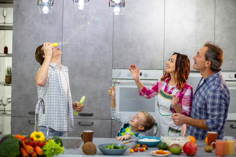 Family time for a beautiful four members in the the modern kitchen making bubbles and have a good happy mood stock photos