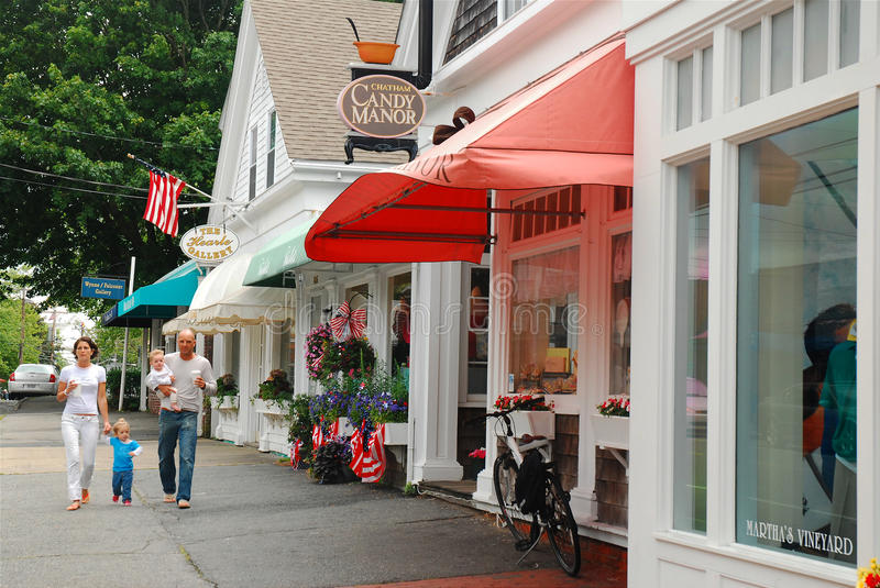 Family time in Cape Cod. A family of four walks in the business district of Chatham, on Cape Cod, Massachusetts, passing boutique stores and a candy shop royalty free stock image