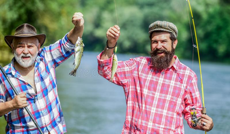 Family time. Fisherman with fishing rod. Activity and hobby. Mature man with friend fishing. Summer vacation. Happy royalty free stock photo