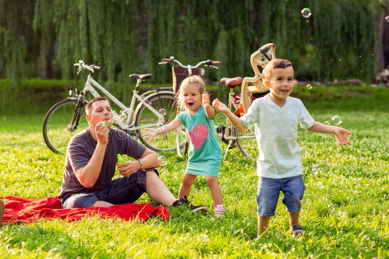 Family time- father with children blow soap bubbles outdoor. Family time- Happy father with children blow soap bubbles outdoor royalty free stock photography
