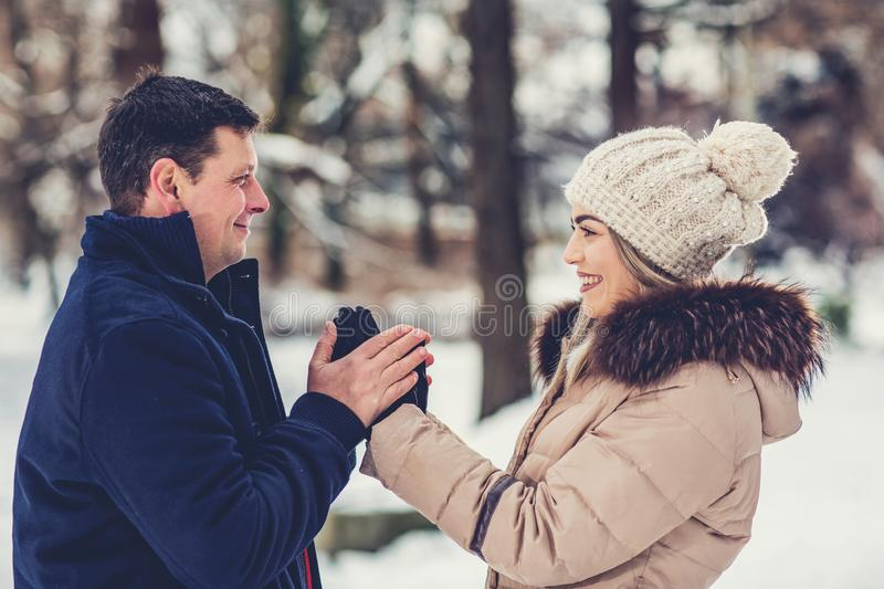Family time - Loving couple enjoying together during winter holidays vacation outside in snow park. stock photo