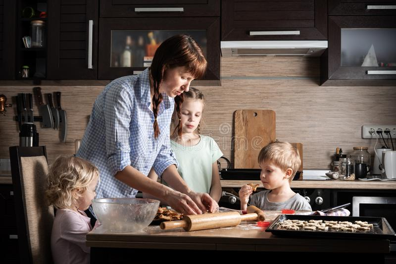 Family time: Mom with three children preparing cookies in the kitchen. Real authentic family. Family : Mom with three children preparing cookies in the kitchen royalty free stock image