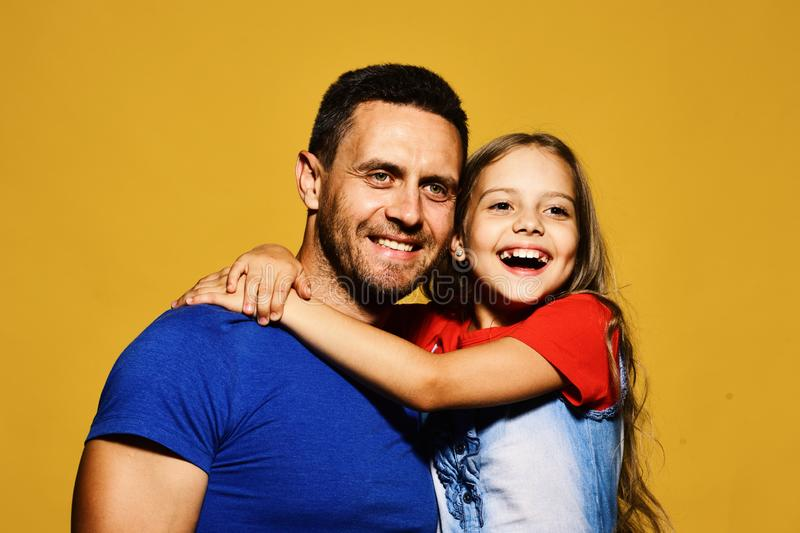 Family time and parenthood concept. Man and girl hug. On yellow background. Dad and daughter with wide smiles. Father and child with happy and cheerful faces royalty free stock images