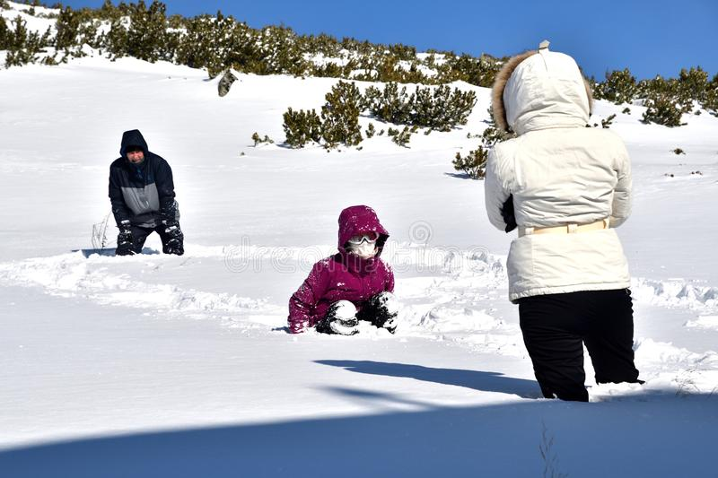 Family playing tumble on the snow in mountains. Family to climb and tumble on the snow in mountains stock photos